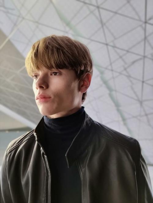 Bőrkabátot viselő férfi, portré módban fényképezve, háttérfüggöny effektet alkalmazva.