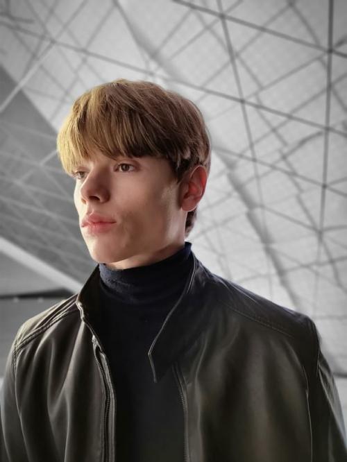 Bőrkabátot viselő férfi, portré módban fényképezve, színpont effektet alkalmazva.