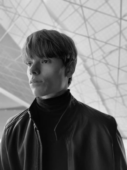 Bőrkabátot viselő férfi, portré módban fényképezve, high-key mono effektet alkalmazva.