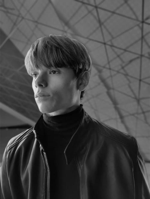 Bőrkabátot viselő férfi, portré módban fényképezve, low-key mono effektet alkalmazva.