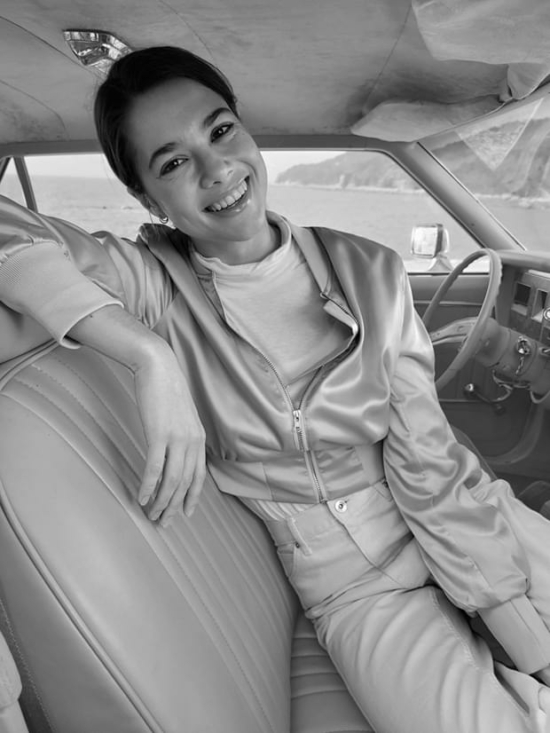 Egy nő a vezetőülésben ülve, Portré módban felvéve, monó High-Key effektussal.