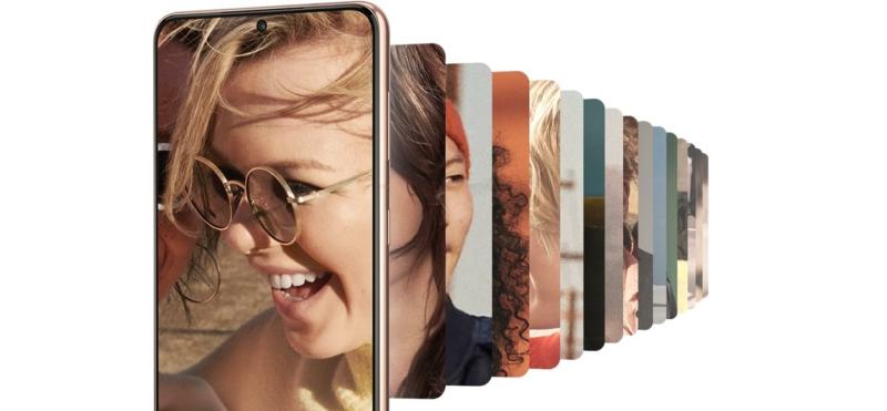 A Galaxy S21 Plus 5G elölről nézve, a képernyőn egy nevető nő képével. Képekből álló galéria látható mögötte.